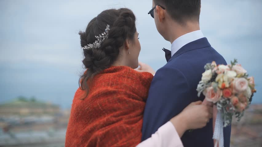 Couple standing on the roof. Happy bride and groom looking to the city from high altitude. Back niddle view | Shutterstock HD Video #30905128