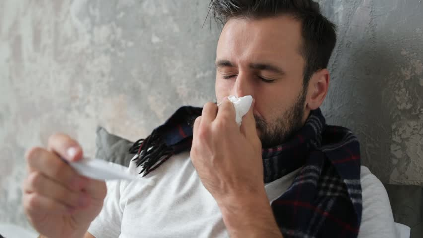 Close up of sick man checking temperature