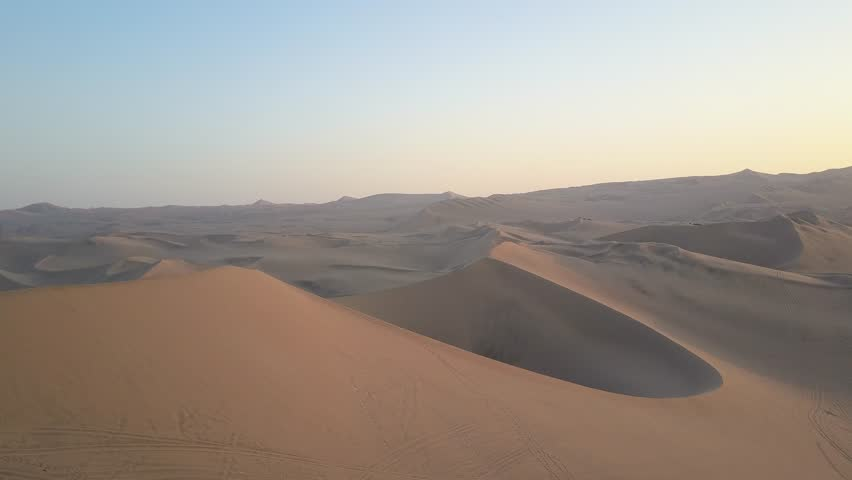 Aerial drone footage on a sunny day above sand dunes of Peru. Close to Ica and Huacachina. Similar to Sahara and Emirates Deserts. Boogie cars driving and people sandboarding. Oasis nearby. #30910528