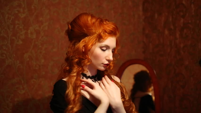 Portrait of a woman with long red curly hair in a black and red dress and choker on her neck. Red-haired girl with pale skin, blue eyes, a bright unusual appearance and red lips