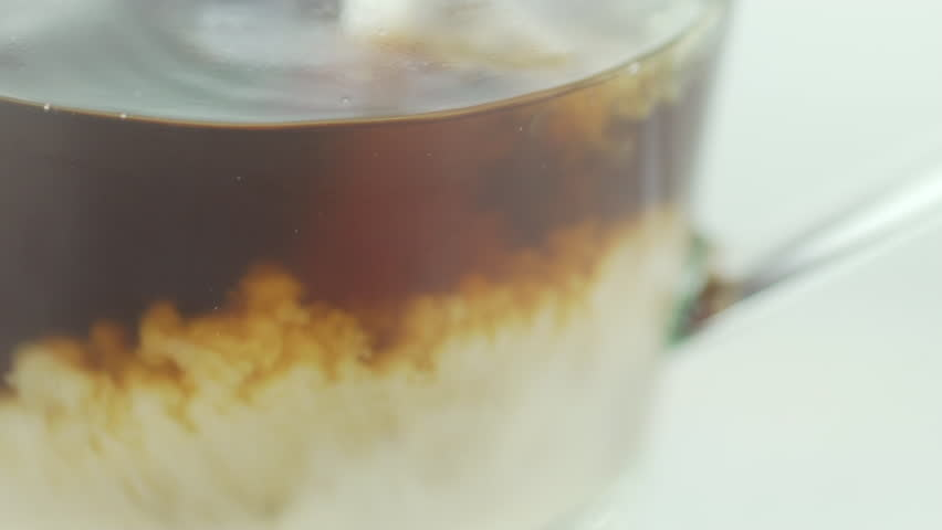 Milk and coffee. Cappuccino. Great macro slow-motion shot of pouring fresh milk into a glass transparent mug with coffee or tea inside of it. Slow motion in a white background.