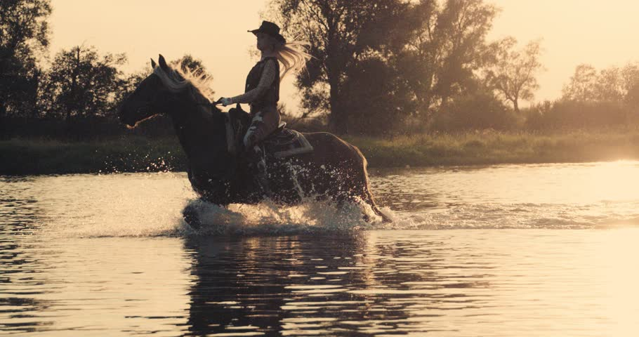 Slow motion 240fps shot.Woman wearing cowboy outfit riding horse on the background of beautiful sunset and water. Girl model on horseback on river water at sunset, backlit with sunshine.