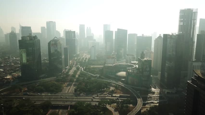 JAKARTA, Indonesia. September 14, 2017: Beautiful aerial scenery of office buildings and Semanggi bridge from a drone flying to left in the misty morning | Shutterstock HD Video #30938488