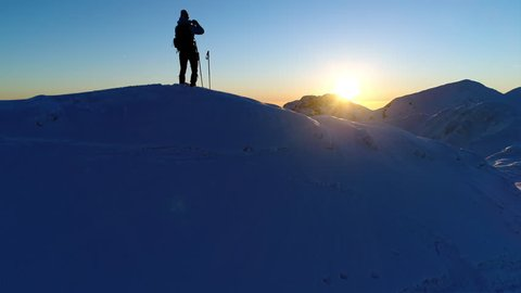 Aerial - Male mountaineer standing on top of snowy mountain and taking photos of beautiful winter scenery with his phone at sunset