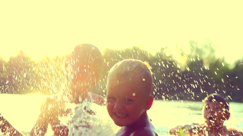 Little boys having fun in water outdoors, kids swimming together, Happy Children joyful little boys playing in River Water. Summer holidays. Summertime fun. Slow motion video 4K, UHD high speed camera