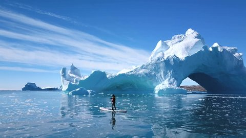 Aerial - Stand Up Paddleboarder paddling around a majestic iceberg with arches in arctic east greenland