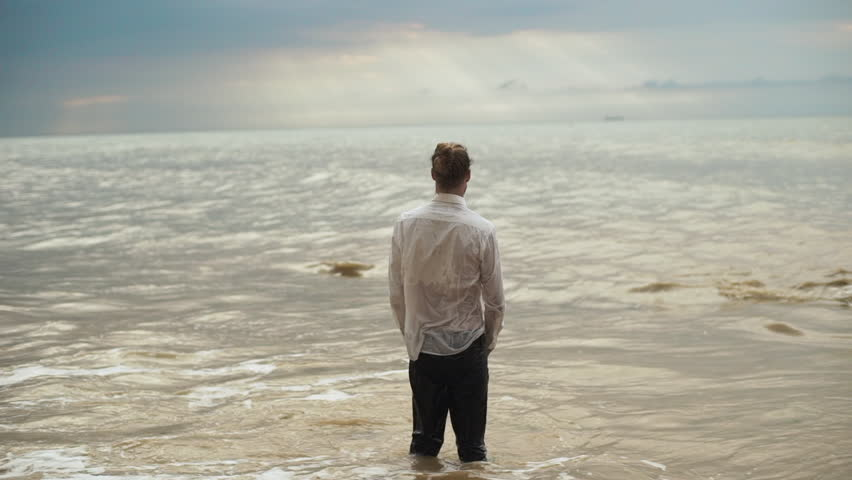 man with tied hair in clothes standing into sea and greeting force of nature with open arms feeling free in slow motion. out of the ordinary