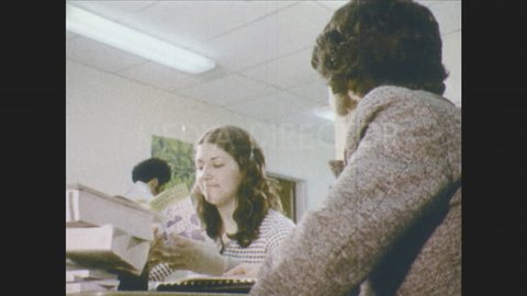 1970s: Girl looks at pamphlet and speaks. Woman instructs girl in archery. Girl shoots arrow. Bulls-eye. School buses leave parking lot. Teenagers get in car.
