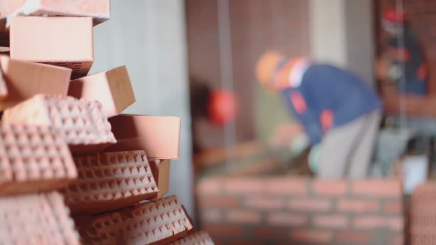 Stack of bricks at background of few workers build wall unfocused