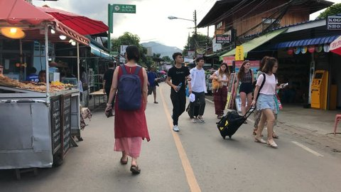 Pai, Thailand _ June 20 2017 : Tracking shot of Walking Street with food vendors and tourists in Pai, Thailand
