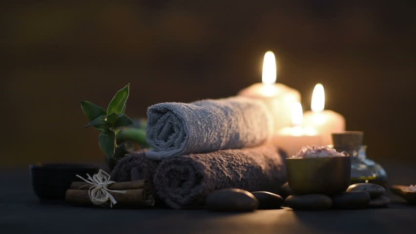 Brown towels with bamboo and candles for relax spa massage and body treatment. Beautiful composition with candles, spa stones and salt on wooden background. Spa and wellness setting with massage oil.