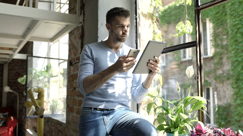 Man in blue sweater using two electronics while sitting on window's sill, steadycam shot  | Shutterstock HD Video #30992248