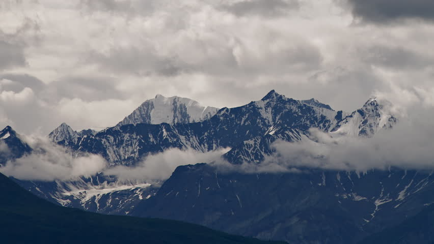 Time lapse of wickedly intense clouds roiling and flowing over peaks of the