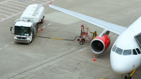DUSSELDORF, GERMANY - JULY 21, 2017: Top view of airport service man take the fuel hose and move it to the aircraft wing. Use the stairs.