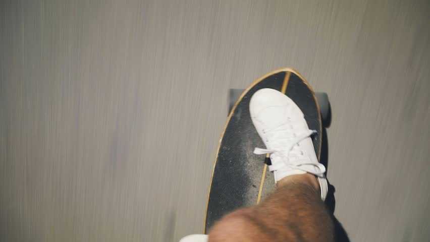 Top view handheld shot of man in white sneakers or skaters shoes rides longboard on asphalt or city tarmac | Shutterstock HD Video #31052098
