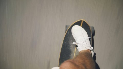 Top view handheld shot of man in white sneakers or skaters shoes rides longboard on asphalt or city tarmac