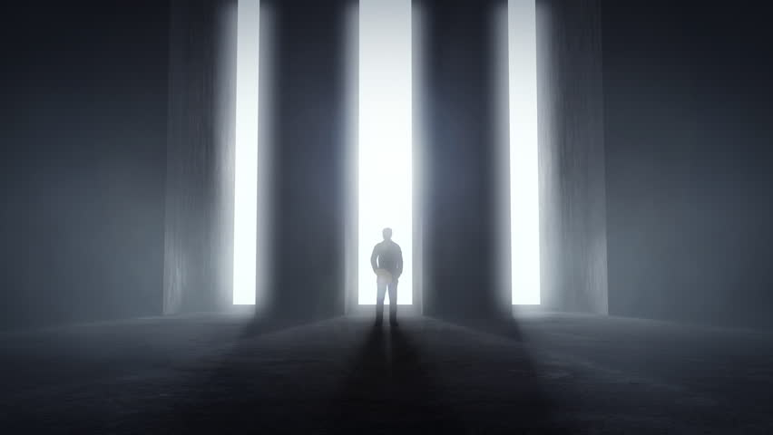Man standing at opening glowing light tunnels in front of a high concrete wall, decision concept