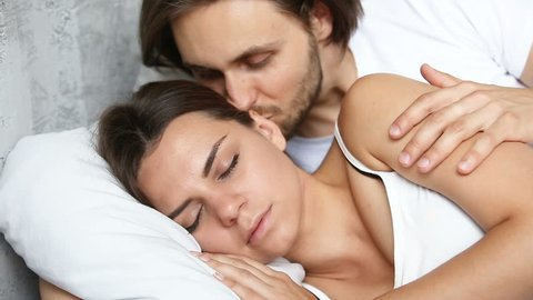 Affectionate husband wakening up sleeping wife by kissing her neck shoulders, young man tenderly touching woman asleep awakening beloved lady, pleasant good morning for happy couple in bed