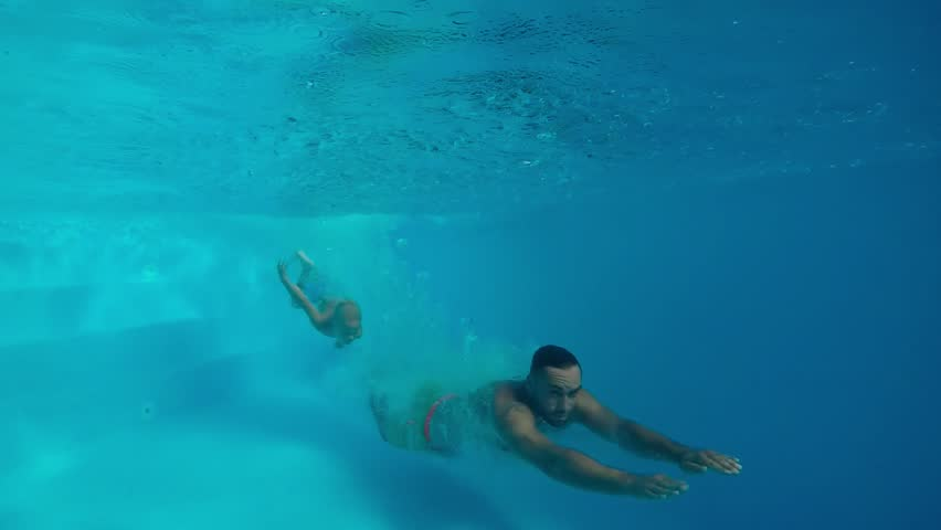 Underwater swimming. Father and son swimming together under water in swimming pool. #31063258