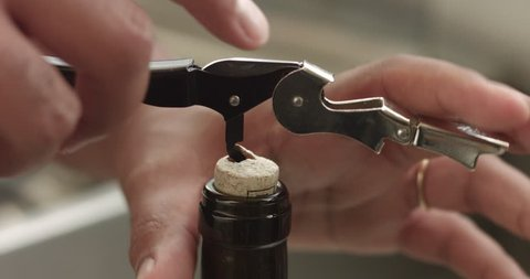 Man's hands pulling a cork out of a wine bottle with a corkscrew
