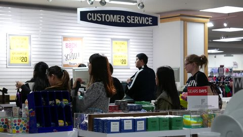 Burnaby, BC, Canada - September 21, 2017 : Motion of people line up for paying item at customer service counter inside Sears store with 4k resolution
