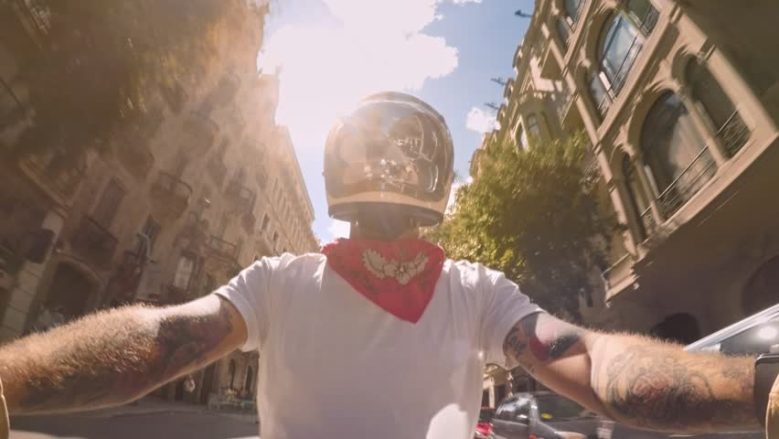 Cool and confident stylish motorcyclist in bandana and white tshirt explores streets of Barcelona on vintage retro cafe racer motorcycle, streets and buildings sweep around him