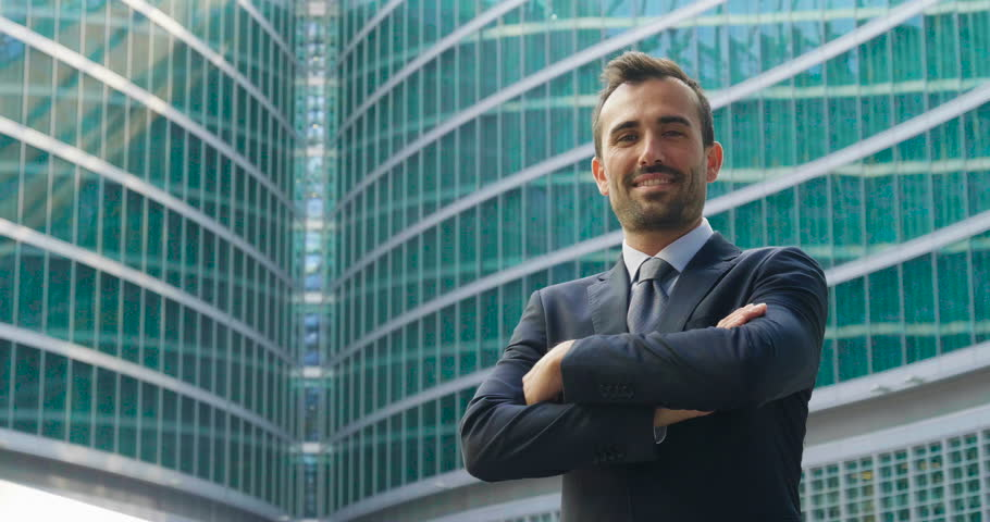 Portrait of a businessman looking at the future proud of his success and smiling. On skyscrapers background with glazed windows. Concept of: business, economy, finance, dreams, future. | Shutterstock HD Video #31095238