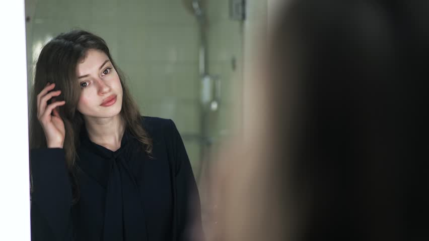 Pensive young woman wearing black clothes is looking at her reflection in a mirror and combing her hair with a hand. Handheld real time close up shot | Shutterstock HD Video #31102588