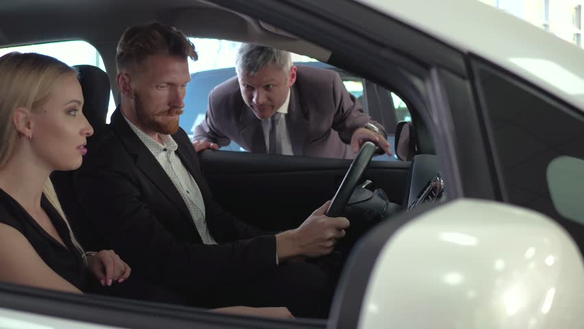 Vehicle Dealer Explaining Car Specification To Young Couple Man