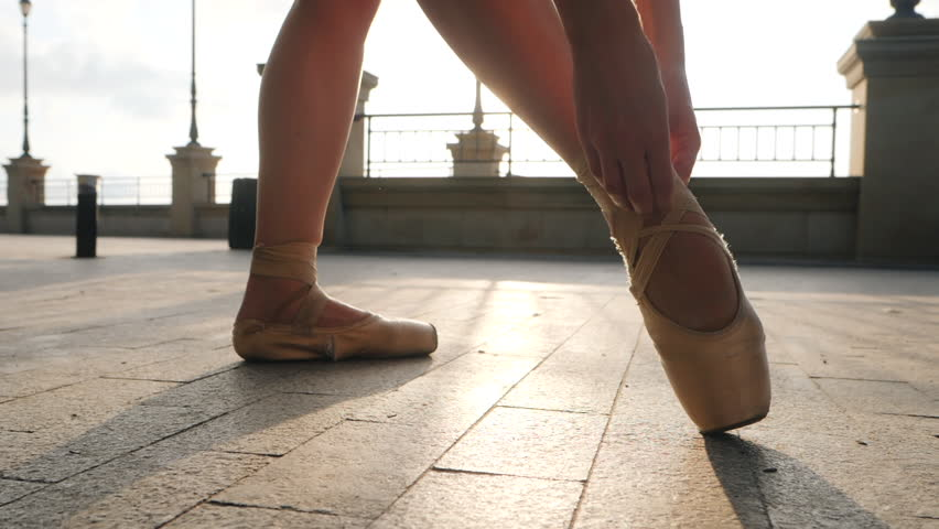 Close up of a ballet dancer's feet as she corrects pointe on the stone embankment. Woman's feet in pointe shoes. Ballerina preparing for classic ballet pas. Slow motion. Flare, gimbal shot