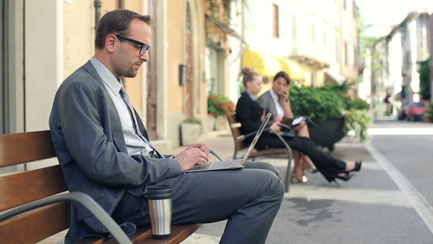 Successful businessman with laptop in the city