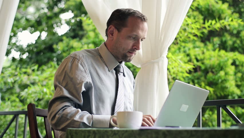 Businessman finishing work on laptop and relaxing on balcony  | Shutterstock HD Video #3113458