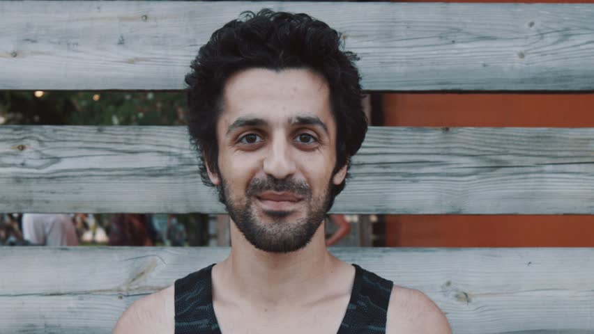 Young arabic bearded man with black curly hair in tank top smiles and waves hand at camera in front of wooden fencing