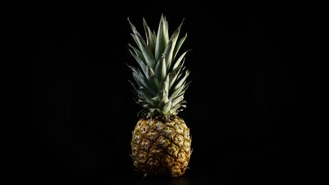 Fresh pineapple spinning on black background