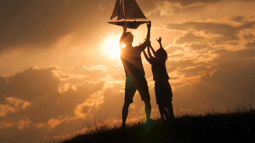 Model of a sailboat. A man is holding a ship model against the sky. The father gives the ship to the child. Backlight. Silhouettes of people against the sky and the sun. | Shutterstock HD Video #31162987