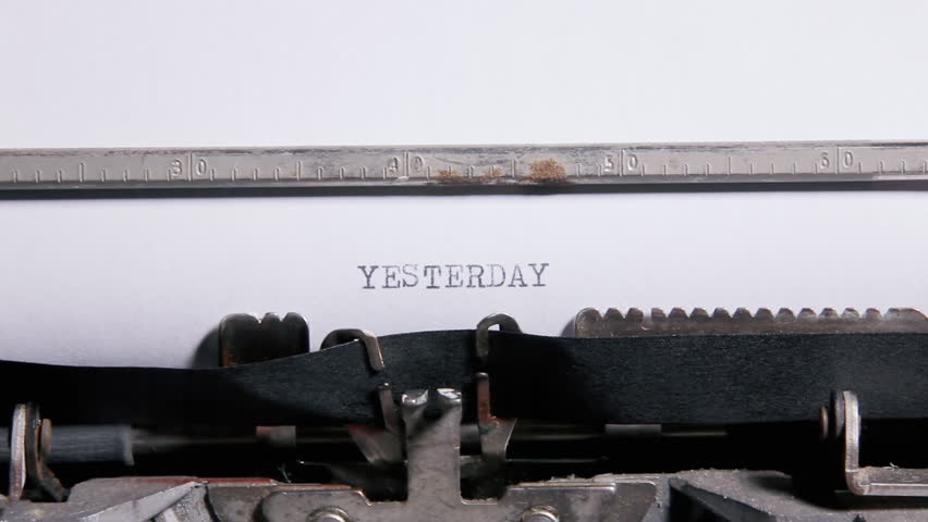 Typing the words - Yesterday Today Tomorrow - on a sheet of paper with an old vintage typewriter.
