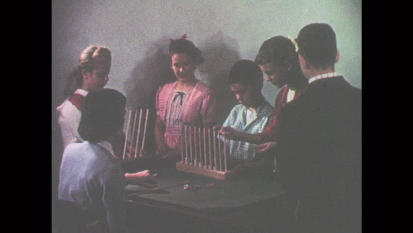 1950s: UNITED STATES: young people use abacus to count. Boy places beads on open ended abaci. Groupings on abacus