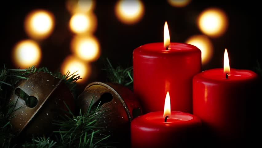 three red christmas candles flicker alongside christmas bells and greenery with white christmas lights in the soft focused background merry christmas - Candle Christmas Lights