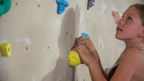 A young student is enjoying her time in a climbing class. She's reaching for the next climbing stone and is trying to get to the top.