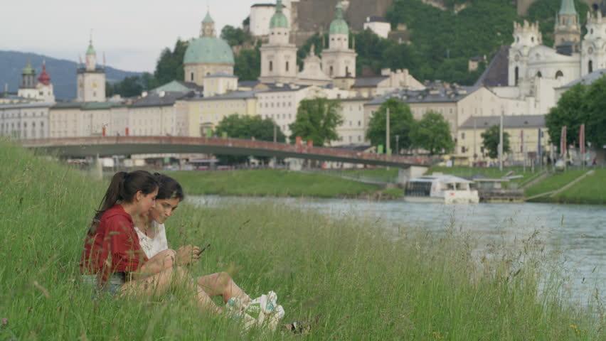 Wide shot of women sitting near river examining photographs on cell phone / Salzburg, Austria | Shutterstock HD Video #31210888