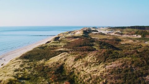 Aerial flying over a long quiet and natural beach in Zeeland, The Netherlands