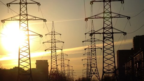 Electric support of high voltage power cables. Energy industry. Production, distribution and transmission of electricity. power lines. Power substation in the big city during sunset