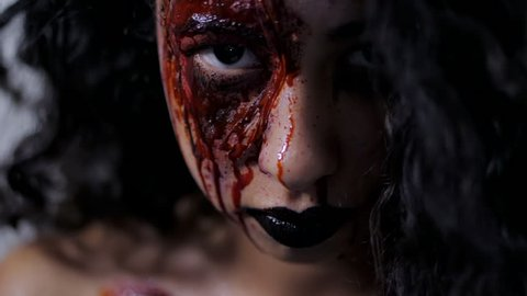 Scary portrait of young girl with Halloween blood makeup. Beautiful latin woman with curly hair looking into camera in studio. Living dead greasepaint. Slow motion.
