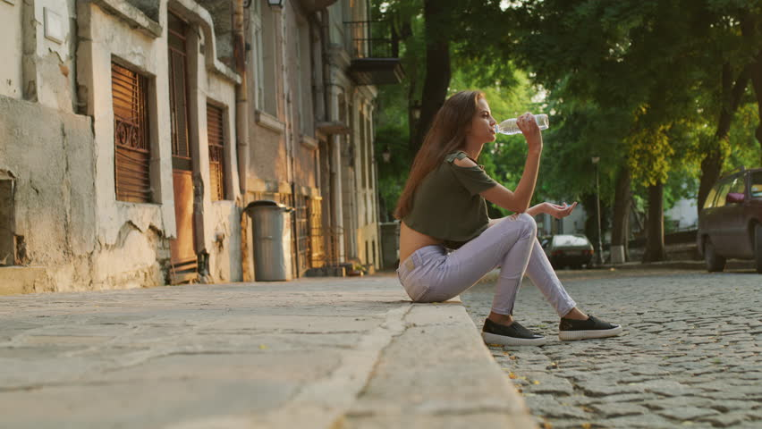 Wide surface level shot of woman sitting on curb drinking water / Plovdiv, Bulgaria