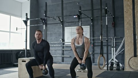 Slowmo shot of strong woman lifting up kettlebell while exercising with personal coach in cross training gym