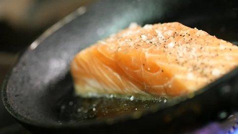 A salmon steak frying in a frying pan