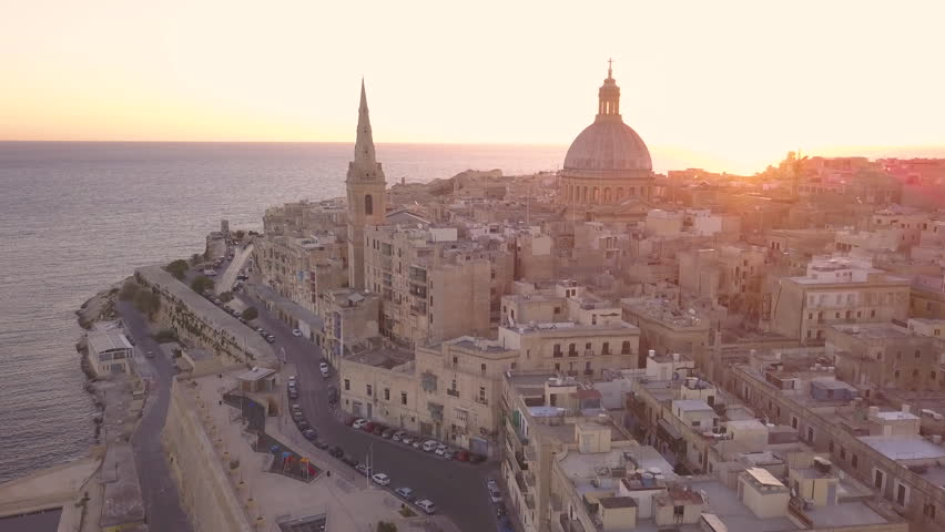 dawn flying between iconic Carmelite church dome and steeple in Valletta Malta