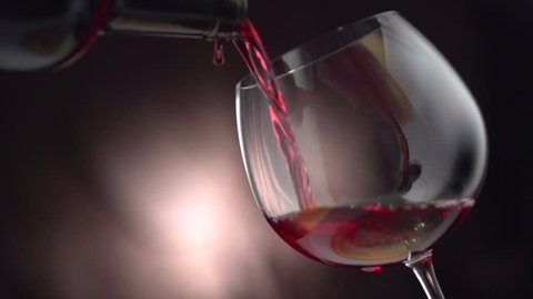 Wine. Red wine pouring in wine glass over dark background. Rose wine pouring from the bottle. Full HD 1080p, slow motion 240 fps