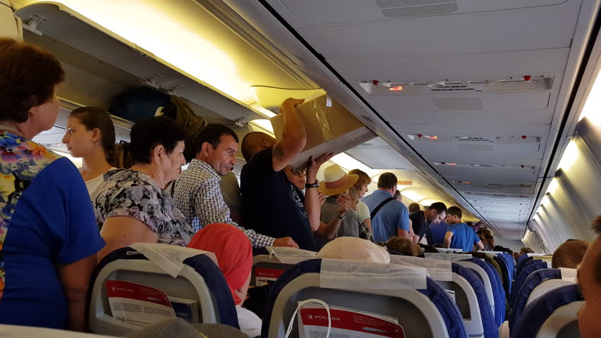 ROSSIYA AIRLINES FLIGHT, RUSSIA - CIRCA SEP 2017: Interior of airplane economy class cabin with passengers. People rushing to deplane after landing at Krasnodar International Airport