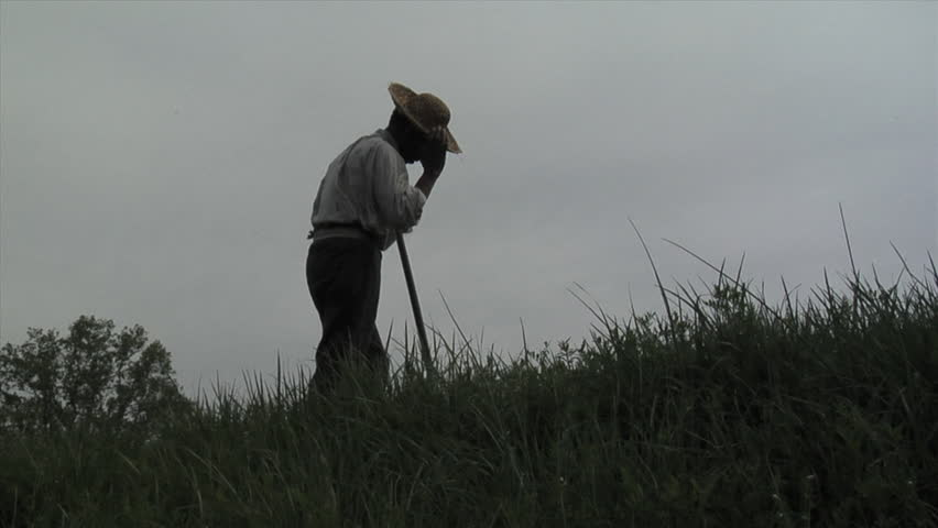 VIRGINIA - 2017. Re-enactment recreation of 1700-1800s Southern American Slavery, slave era. Enslaved African-American. Working in field, laboring in bondage with tool. tattered clothing, Field slave.